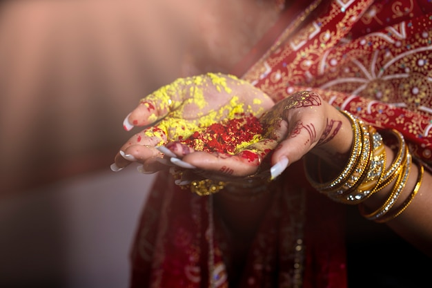 Nahaufnahmehände von indien-mädchen, das buntes pulver in den händen am holi festival hält