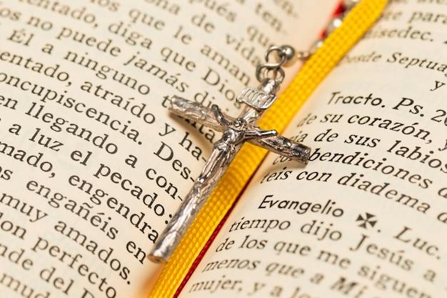 Nahaufnahmehalskettenkreuz und heilige schrift