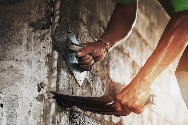 Nahaufnahmehand der arbeitskraft zement an der wand für das errichten des hauses vergipsend