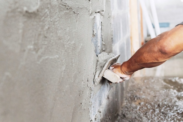 Nahaufnahmehand des arbeiters, der zement an der wand in der baustelle verputzt