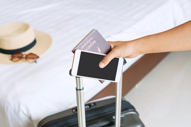 Nahaufnahmehand des jungen asiatischen reisenden, der pass und smartphone im hotelzimmer hält