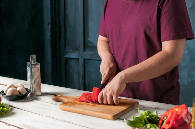 Nahaufnahmehand des kochbäckers, der pizza an der küche macht
