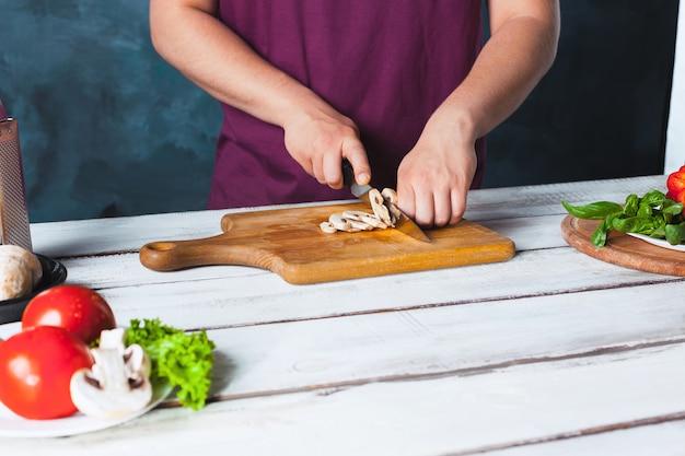 Nahaufnahmehand des kochbäckers, der pizza bei küche macht