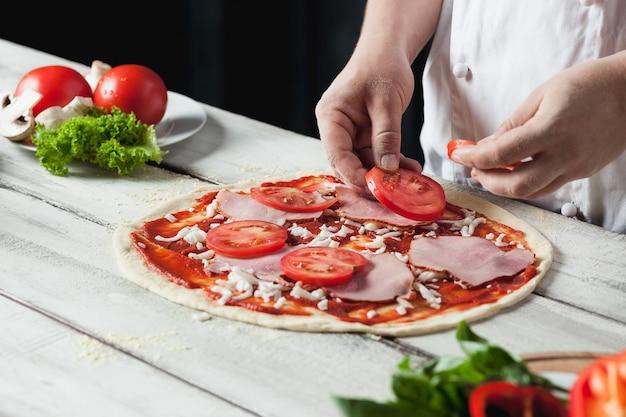 Nahaufnahmehand des kochbäckers in der weißen uniform, die pizza an der küche macht
