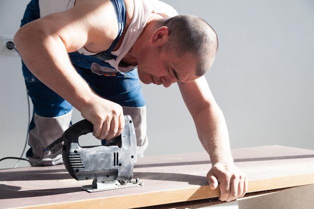Nahaufnahmehand des tischlers mit berufsschneidwerkzeug laubsäge oder laubsäge, schneiden die hölzerne tischplatte und sägen planke, braune archivierungen, sägemehl. fachgerechte installation und reparatur