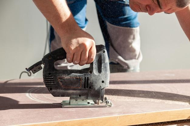 Nahaufnahmehand des tischlers, tischler mit berufsschneidwerkzeug laubsäge oder laubsäge, geschnittene hölzerne tischplatte, sägeplanke, braune archivierungen, sägemehl. loch für spüle in der küche schneiden