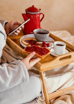 Nahaufnahmehand, die brotscheibe mit marmelade hält