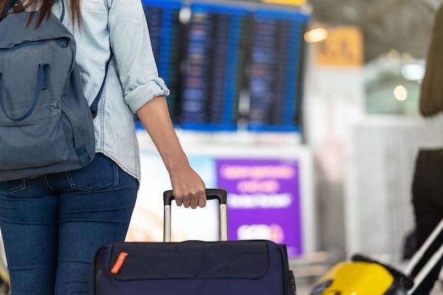 Nahaufnahmehand, die das gepäck über dem flugbrett für abfertigung am flug informat hält