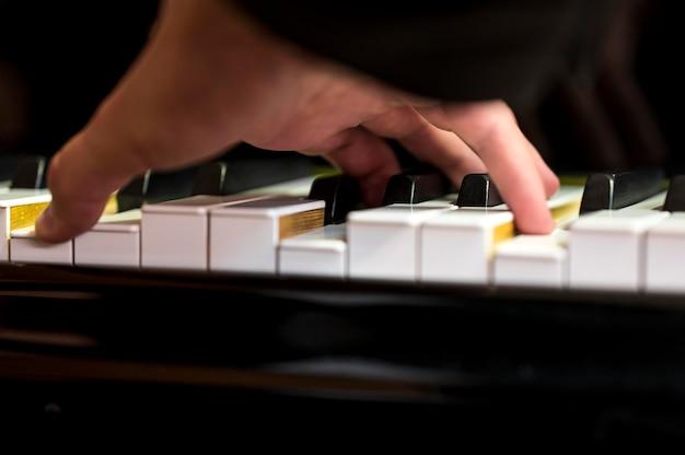 Nahaufnahmehand, die einen akkord auf klavier hält