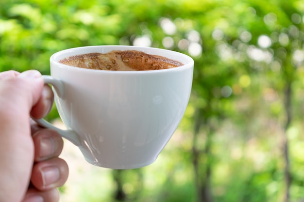 Nahaufnahmehand, die einen tasse kaffee über natürlichem morgenhintergrund hält.