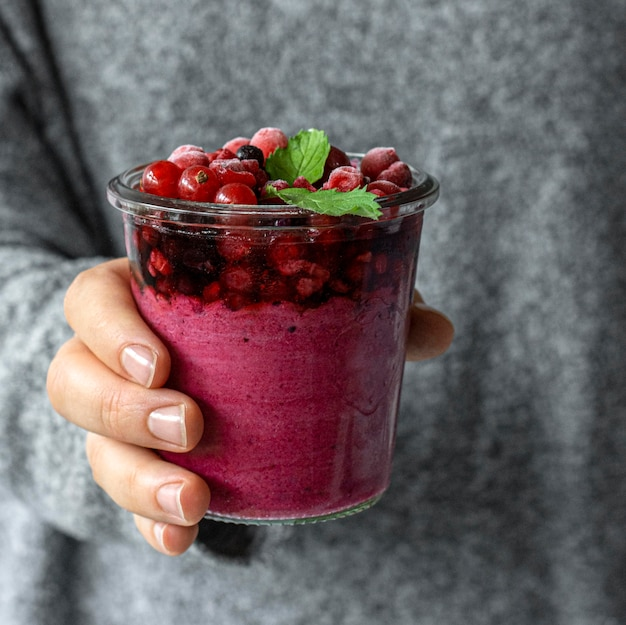 Nahaufnahmehand, die fruchtiges smoothieglas hält