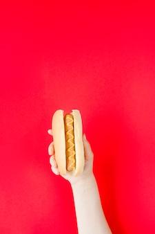 Nahaufnahmehand, die hotdog hält
