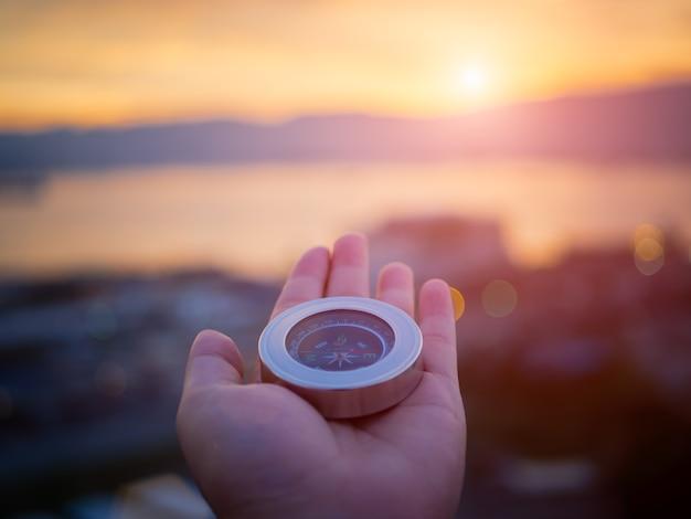 Nahaufnahmehand, die kompass mit gebirgs- und sonnenunterganghimmelhintergrund hält.