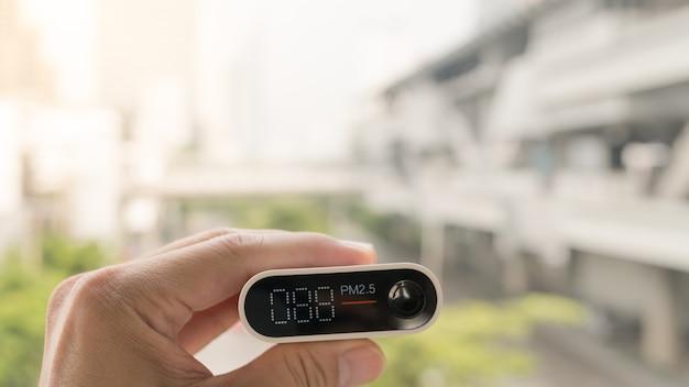 Nahaufnahmehand, die luftqualitätsüberwachung hält, um verschmutzungsgrad oder kleine partikel in der stadt zu erfassen