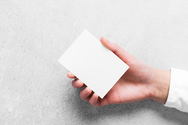 Nahaufnahmehand, die papier-visitenkarte hält