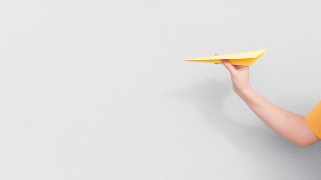 Nahaufnahmehand, die papierflugzeug hält