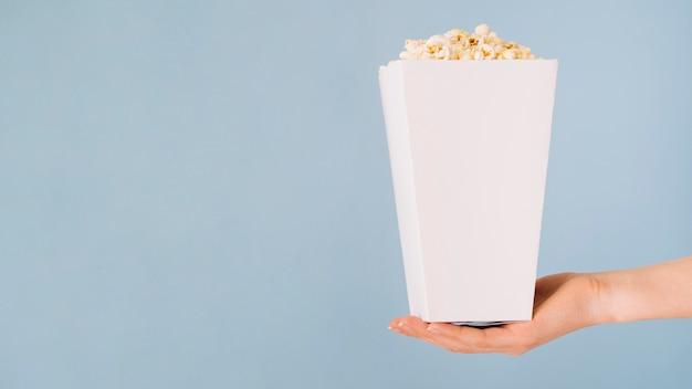 Nahaufnahmehand, die popcornbox hält