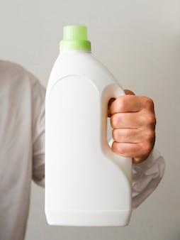Nahaufnahmehand, die reinigungsmittelflaschenmodell hält