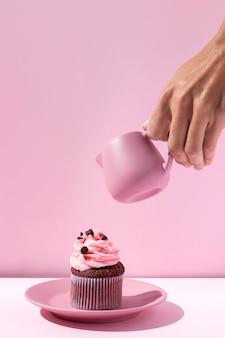 Nahaufnahmehand, die rosa tasse hält