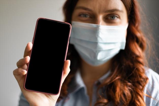Nahaufnahmehand, die smartphone mit schwarzem bildschirm hält. rahmenloses designkonzept für mobiltelefone. frau in medizinischer schutzmaske