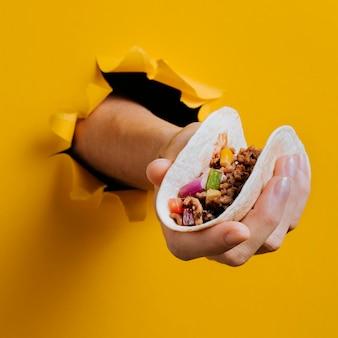 Nahaufnahmehand, die taco hält