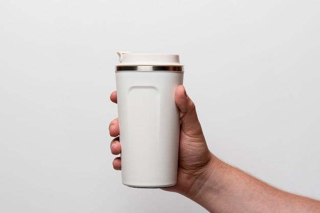 Nahaufnahmehand, die weiße kaffeeflasche hält
