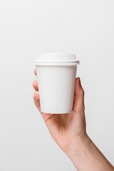 Nahaufnahmehand, die weiße kaffeetasse hält
