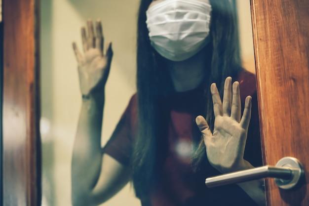 Nahaufnahmehand einer asiatischen frau, die eine medizinische maske trägt und die glastür berührt, wenn sie zu hause isoliert bleibt