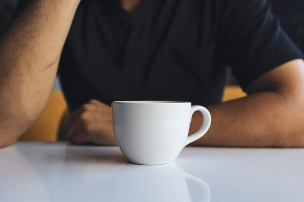 Nahaufnahmehand eines geschäftsmannes, der eine weiße tasse kaffee im raum hält