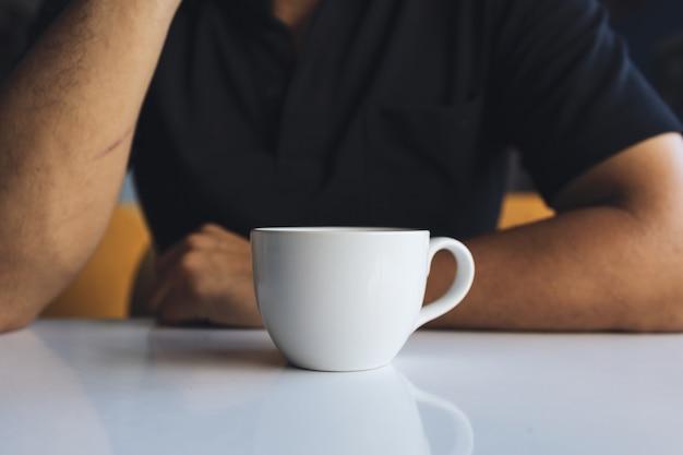 Nahaufnahmehand eines geschäftsmannes, der eine weiße tasse kaffee im raum mit weichzeichner und über licht in der hält