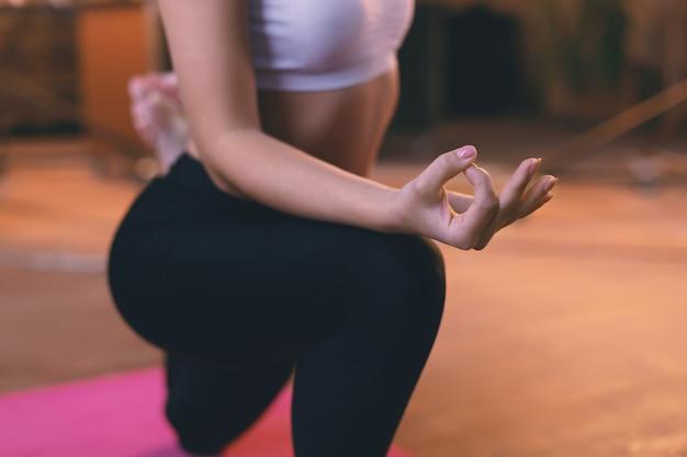 Nahaufnahmehand eines jungen mädchens, das yoga auf dem boden tut