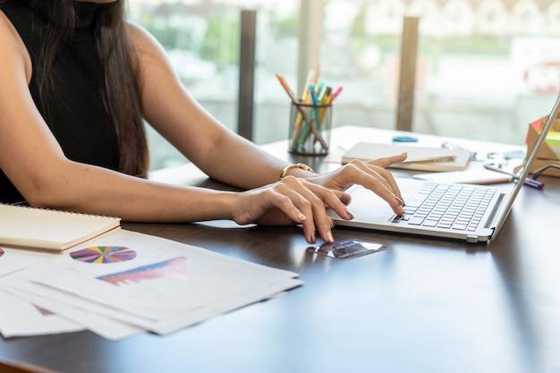 Nahaufnahmehand geben die bestätigung mit technologielaptop und kreditkartenmodell für das einkaufen ein