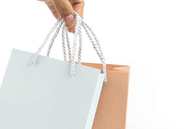 Nahaufnahmehand hält leere papiereinkaufstasche auf einem weißen hintergrund mit kopienraumzusammensetzung.