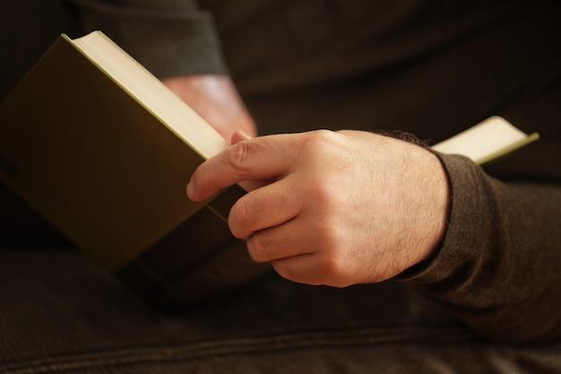 Nahaufnahmehand mit buch, mann, der buch liest