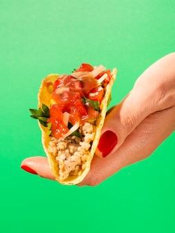Nahaufnahmehand mit taco und grünem hintergrund