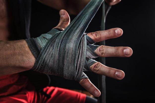 Nahaufnahmehand mit verband des muskulösen mannes, der kickboxen auf schwarz trainiert