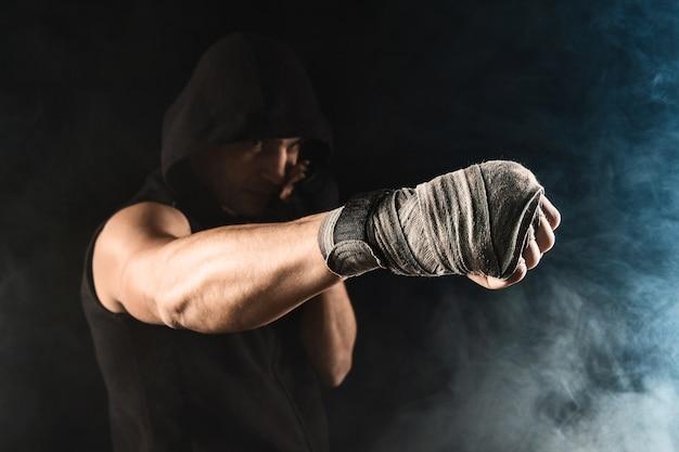 Nahaufnahmehand mit verband des muskulösen mannes, der kickboxen auf schwarzem und blauem rauch trainiert