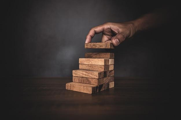 Nahaufnahmehand platziert holzblockturm gestapelt in treppenstufe