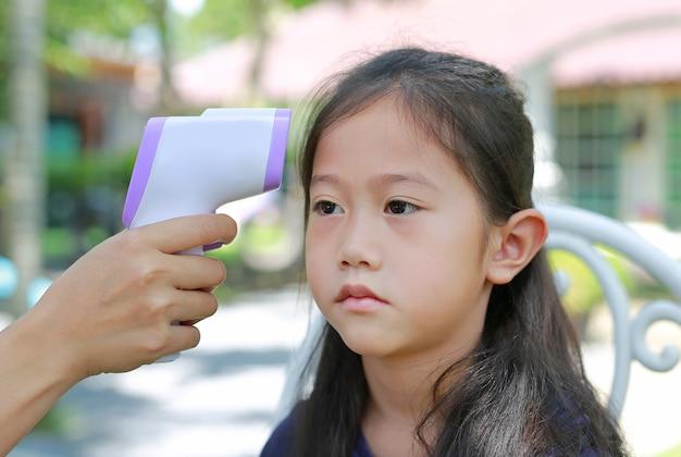 Nahaufnahmehand unter verwendung des infrarot-thermometers, das asiatisches kleines mädchen der stirn misst