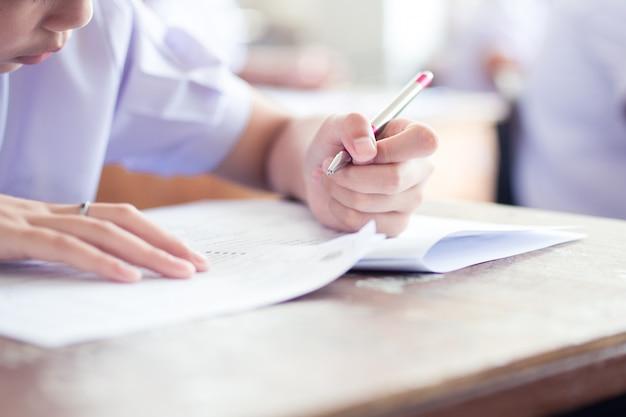 Nahaufnahmehand von studenten, die eine prüfung in klassenzimmer mit druck schreiben