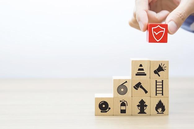 Nahaufnahmehand wählt schutzsymbol auf würfelholzspielzeugblöcken