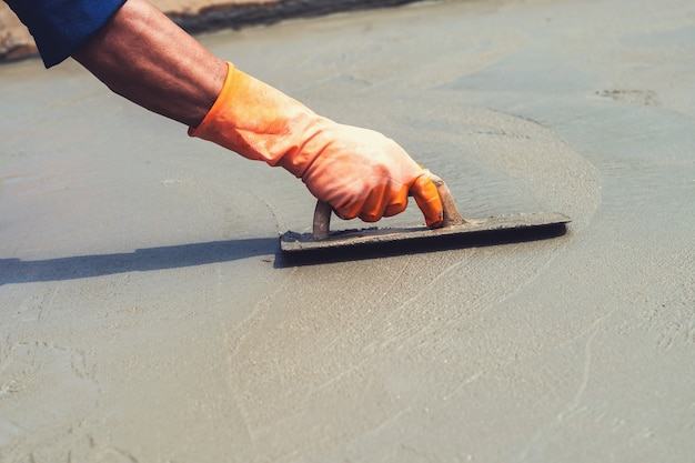 Nahaufnahmehandarbeiter, der betonpflasterung für mischungszement an der baustelle nivelliert