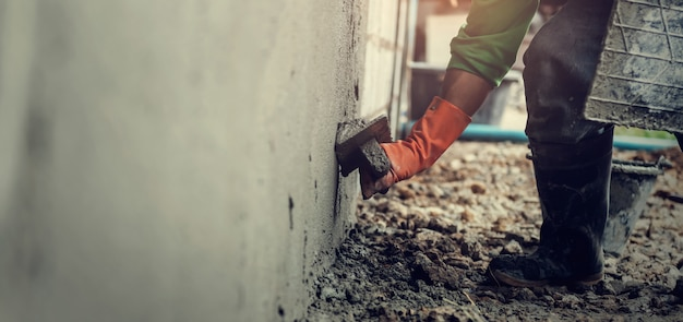 Nahaufnahmehandarbeiter, der zement auf wand für das errichten des hauses vergipst