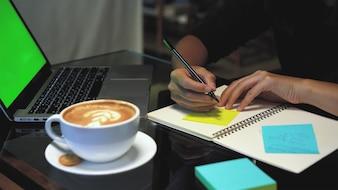 Nahaufnahmehände der asiatischen Geschäftsfrau arbeitend und auf Papieranmerkungen über dem Notizbuch schreibend