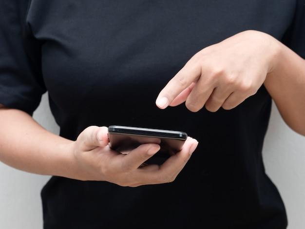 Nahaufnahmehandfrauen-touchscreen auf dem handy für das einkaufen und das spielen von social media