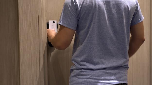 Nahaufnahmehandmann öffnen die tür, nachdem sie eine elektronische sicherheitsschlüsselkarte seines hotelzimmers verwendet haben