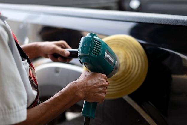 Nahaufnahmehandmann poliert ein schwarzes auto mit einem polierer