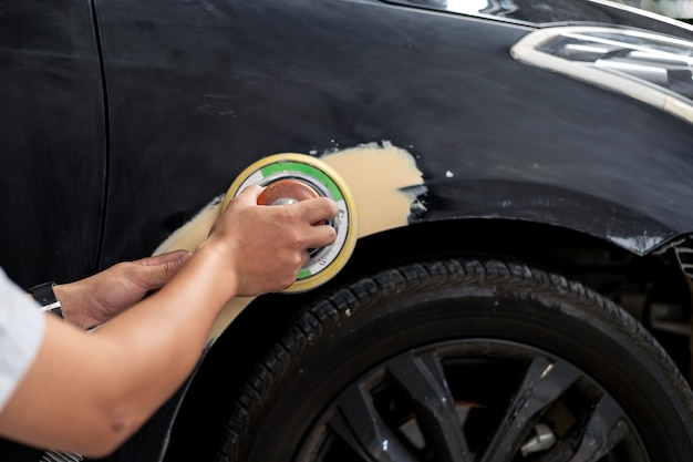 Nahaufnahmehandmechanikerarbeitskraft, die polierautokörper versandet und für das malen am stationsservice sich vorbereitet