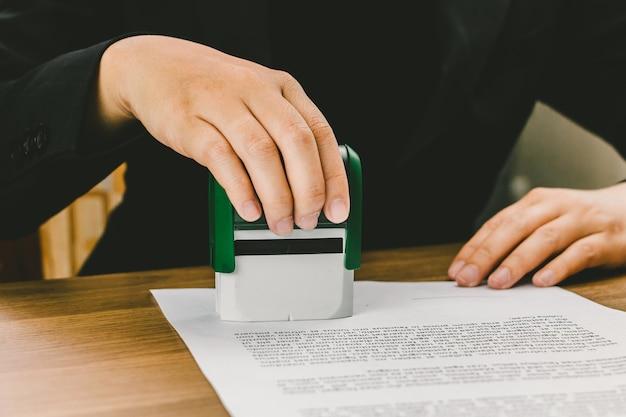 Nahaufnahmehandstempeln der geschäftsfrau für das unterzeichnen der zustimmung auf dokumenten