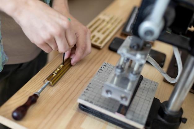 Nahaufnahmehandwerkerhände, die text für das branding von leder mit persönlichem stempel eingeben, der ein handwerksetikett erstellt